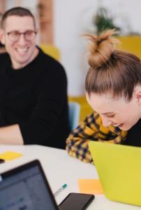 laughing man woman laptop yellow